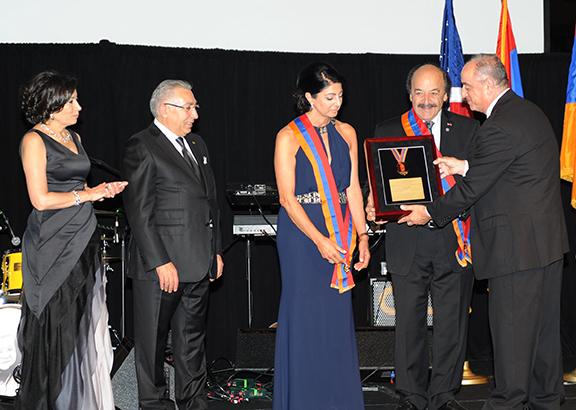 Katcho and Araxi Achajian receive the Navasartian Honorary President plaque from Homenetmen Chairman Maniel Marselian as last year's presidents Varant and Hoori Melkonian look on