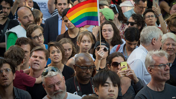 People wave flags during a vigil in reaction to the mass shooting at a gay nightclub in Orlando, Florida, in New York on June 12, 2016. (Source: AFP)