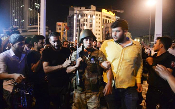 A Turkish soldier, arrested by civilians, is walked to be handed to police officers in Istanbul's Taksim Square, early Saturday. (Photo: AP)