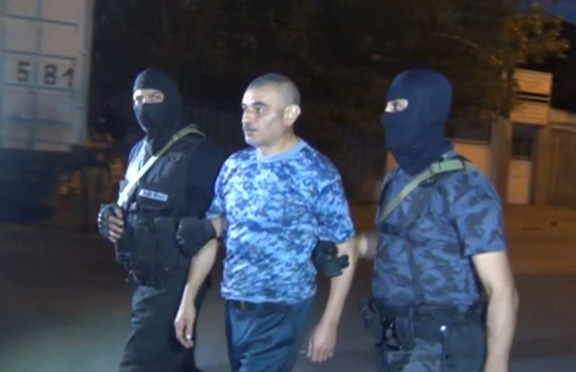 """A member of the """"Daredevils of Sasoun"""" is being escorted by police after the group surrendered Sunday"""