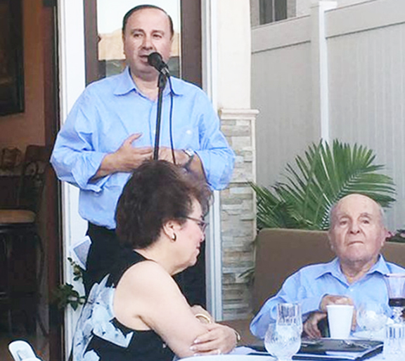 The evening's host Mike Sarian welcomes guests with long-time Asbarez supporter Hacob Shirvanian (foreground) and his daughter Alice Petrossian