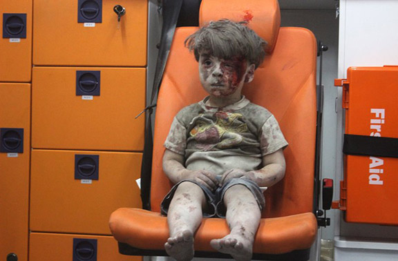 Five-year-old boy, Omran Daqneesh, sits in an ambulance after reportedly being pulled out of a building hit by an airstrike in Aleppo on August 18, 2016. (Photo: Mahmoud Raslan/Getty Images)