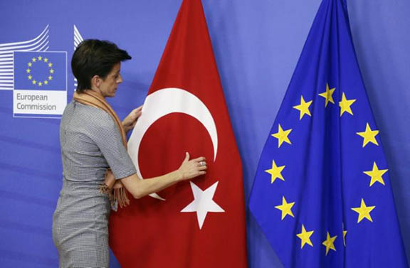 A woman adjusts the Turkish flag next to the European Union flag at the EU Commission headquarters in Brussels (Photo: Reuters/Francois Lenoir)