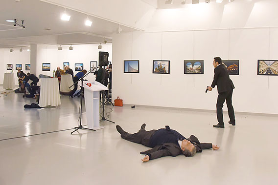 The man on the right, identified as the shooter, stands over the body of Ambassador Andrey Karlov (Getty Images)