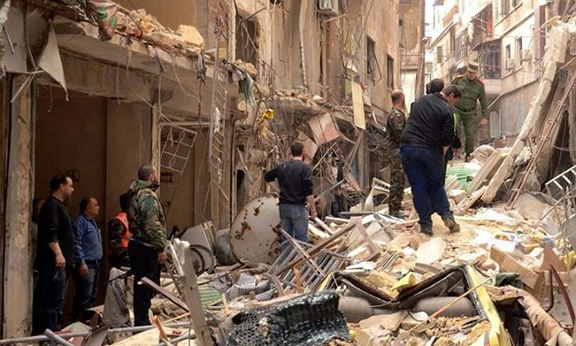 Syrians walk through the rubble following reported rocket attacks by rebel fighters in northern Aleppo. (Photo: George Ourfalian/AFP/Getty Images)