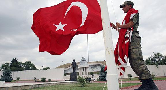 Serviceman raising Turkish flag (Photo: AP Photo/Burhan Ozbilici)