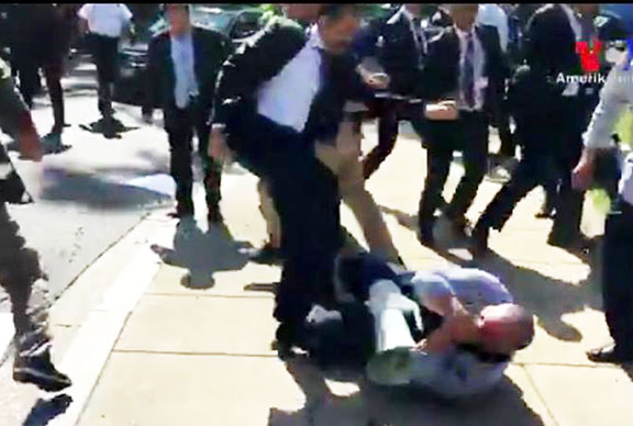 A protester being kicked by a pro-Erdogan attacker