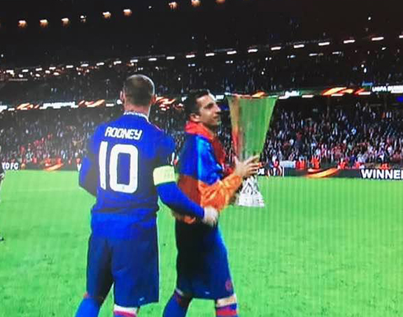 Draped in the Armenian tri-color, Henrikh Mkhitaryan carries the UEFA Europa League  trophy on the field