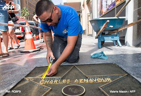 A worker lays concrete ahead of placing Charles Aznavour's star