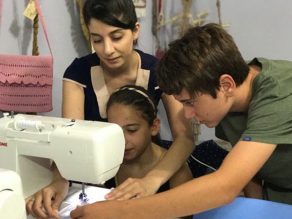 Joseph teaching a student how to use the sewing machine