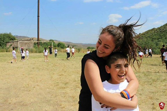 An AYF Youth Corps volunteer with one of the many local children impacted by the program