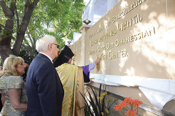 Prelate Marditossian blesses the sign baring the new center name