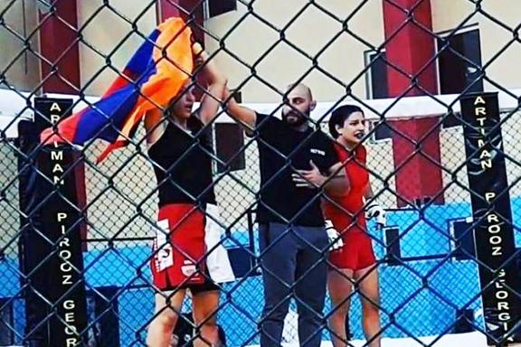 Armenia's Karine Karapetyan (left) waves the Armenian flag after beating Azerbaijan's Rena Safarova, the sister of ax-murderer Ramil Safarov