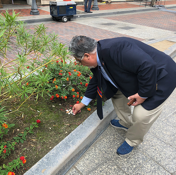 State Senator Anthony Portantino places stones he brought back from Artsakh at the foot of the Artsakh Avenue sign