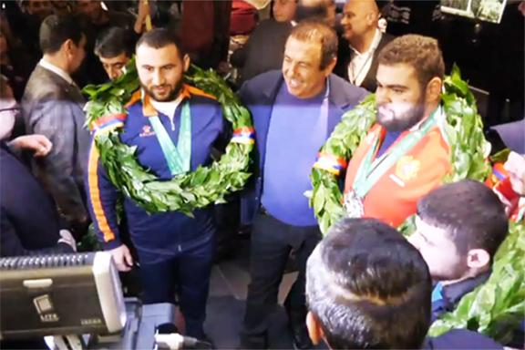 World Champ Simon Martirosyan (left) with his teammates and Armenia's National Olympics Chair Gagig Tsarukian at Zvartnots Airport on Monday
