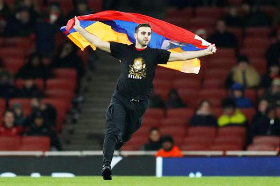 An Armenian rushes the field with an Artsakh flag after Arsenal beats the Azerbaijani soccer team, Qarabag