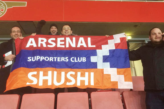 Arsenal fans display the Artsakh flag from bleachers during the match with Azerbaijan
