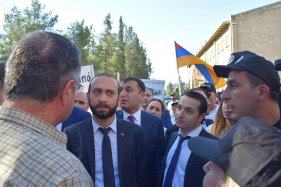 Parliament Speaker Ararat Mirzoyan and lawmaker Mkhitary Hayrapetyan are confronted by angry protesters in front of the Melkonian School on July 5