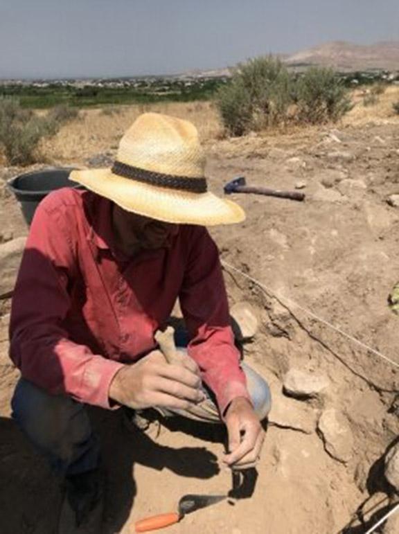 Dr. Cobb excavates and examines a bone. Photo Credit: Yadian Wang