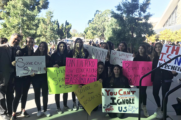 """AGBU MHS students protested with signs that read """"We Will Not Assimilate,"""" and """"Save Our School!"""""""