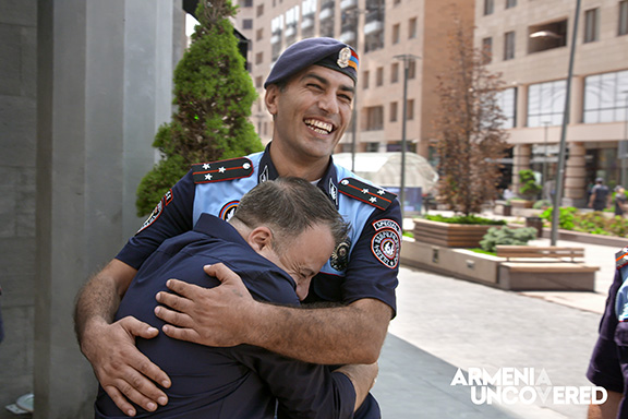 Kev Orkian embracing an Armenian police officer