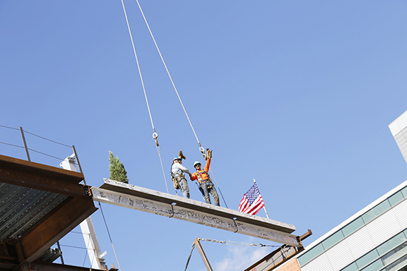 Beam is being listed to be hoisted with a tree, also adorned with the American flag