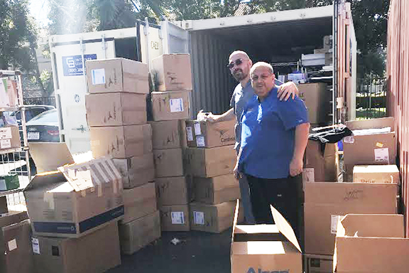 CCSC Administrator Raffi Sarkissian and surgery technician Vardan Lalayan reviewing boxes of supplies bound for Armenia in response to the COVID-19 containment efforts