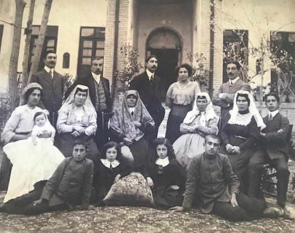 The family of the author's grandfather, pictured standing in the far left, with his wife holding a newborn